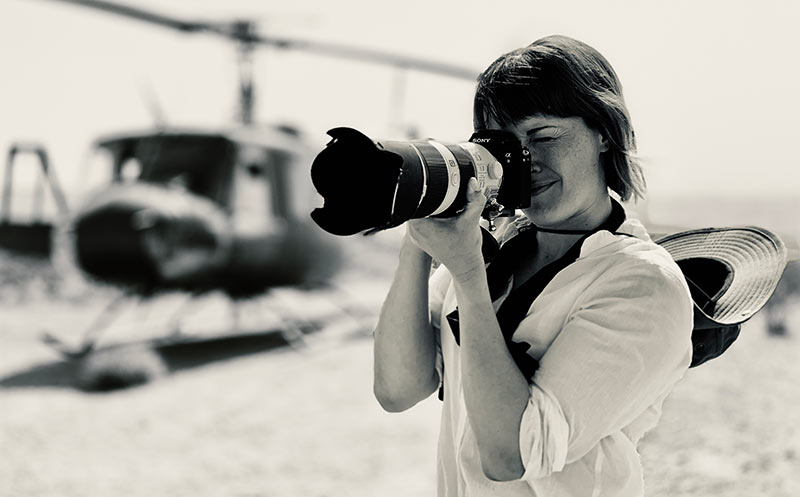 Portrait of unit stills photographer, Aimee Spinks, taking a photo in front of a helicopter.