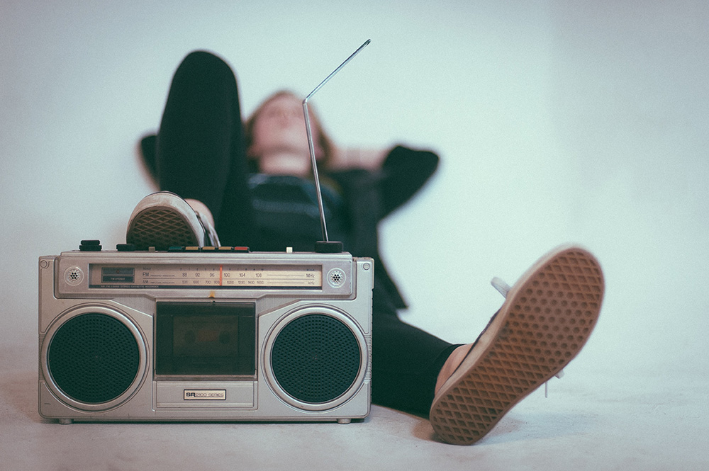 A person relaxing with one foot propped up on a radio